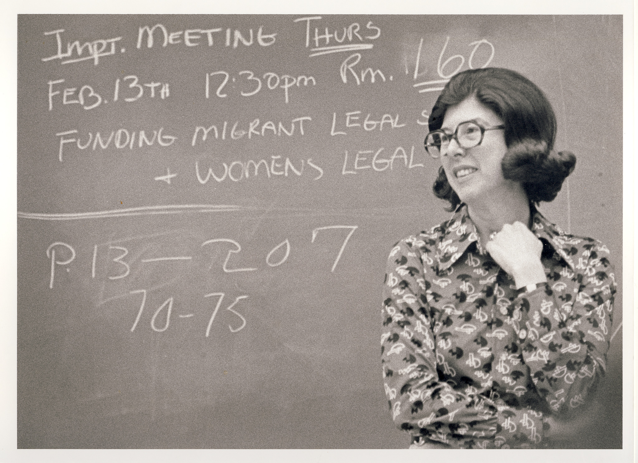 Photo: Herma Hill Kay standing in front of a chalk board smiling
